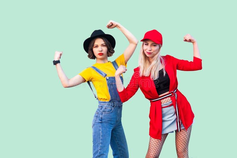 一起花费了不起的时间的最好的朋友 站立和显示那里力量的两个美丽的时兴的行家女孩画象, 免版税图库摄影