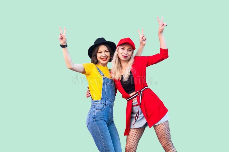 一起花费了不起的时间的最好的朋友 站立和显示v的两个美丽的愉快的时兴的行家女孩画象唱歌, 免版税库存图片
