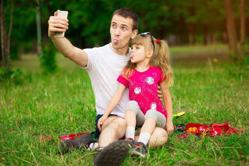 一起花费时间本质上,采取selfies和做鬼脸的父亲和女儿 免版税库存照片