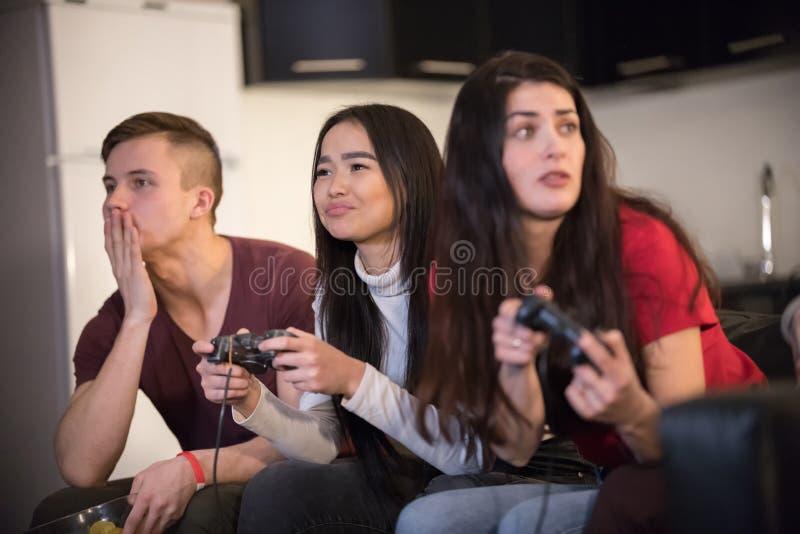 一起花费时间的年轻朋友公司  两打比赛的年轻女人使用控制杆和年轻人气喘 图库摄影
