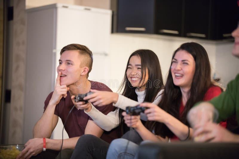 一起花费时间的年轻朋友公司  两打比赛的年轻女人使用控制杆 兴奋 库存照片