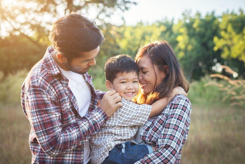 一起花费时间的愉快的年轻家庭外面在绿色natur 免版税库存照片