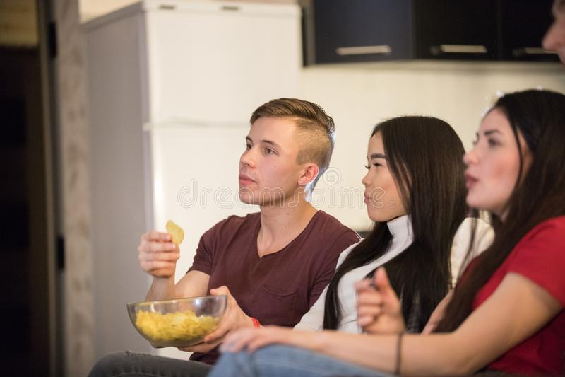 一起花费时间看着电视和吃玉米花和芯片的年轻朋友公司  库存图片