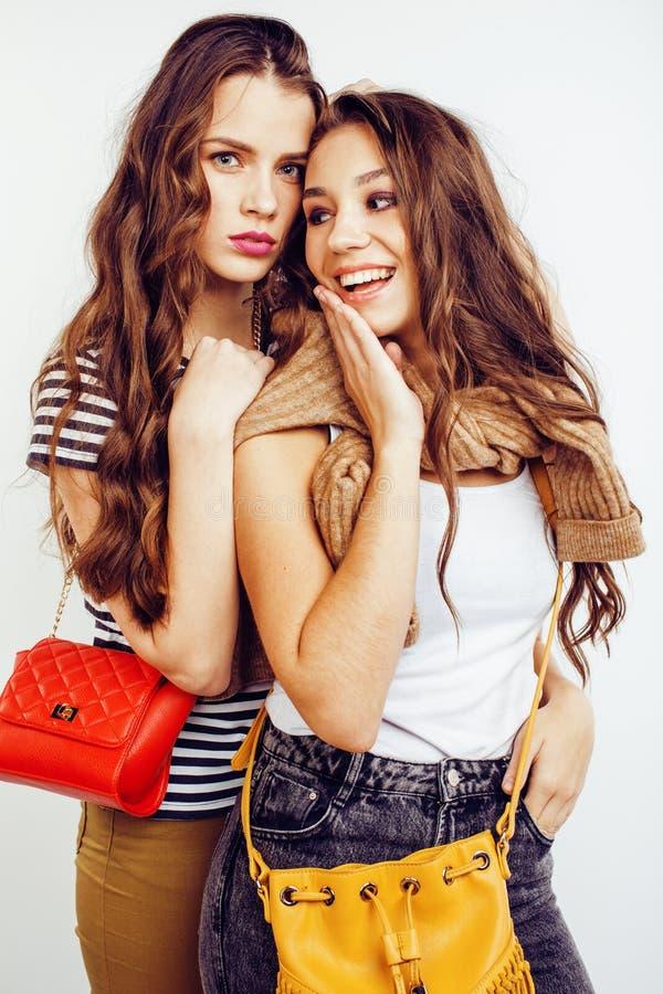 一起获得两个最好的朋友的十几岁的女孩乐趣,摆在情感在白色背景, besties愉快微笑 免版税库存照片