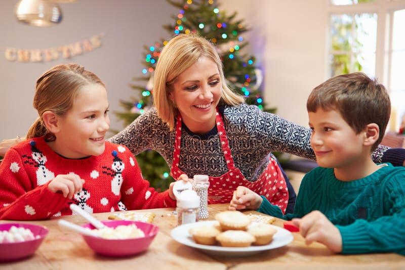 一起装饰圣诞节曲奇饼的母亲和孩子 库存图片