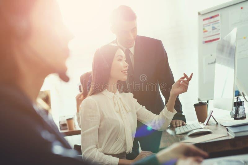 一起观看在一个屏幕上的女孩操作员和人在办公室 免版税库存图片