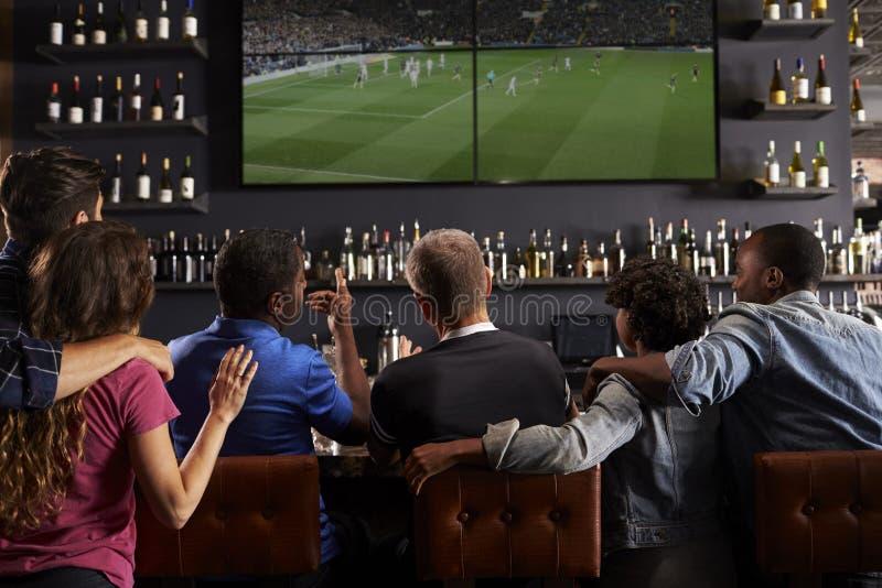 一起观看在酒吧的朋友背面图屏幕 免版税库存照片