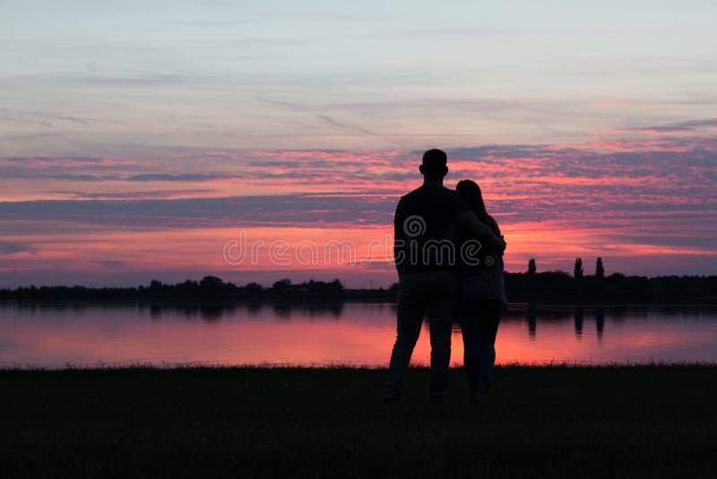 一起观看日落的年轻夫妇 免版税库存照片