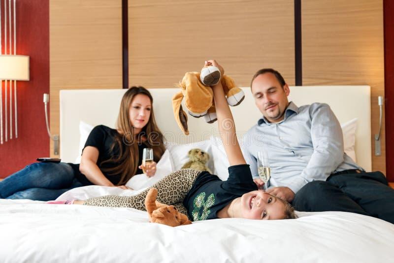 一起说谎在床上的父亲、母亲和女儿年轻愉快的微笑的白种人家庭在旅馆卧室,当有假期时 库存照片