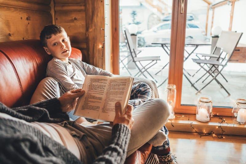 一起说谎在舒适沙发的父亲和儿子看书在温暖的乡间别墅里 对孩子概念性图象的读书 免版税库存图片