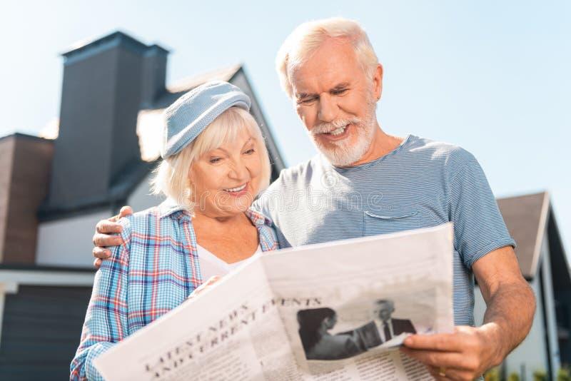 一起读他们的早报的退休的愉快的夫妇房子外 免版税库存照片