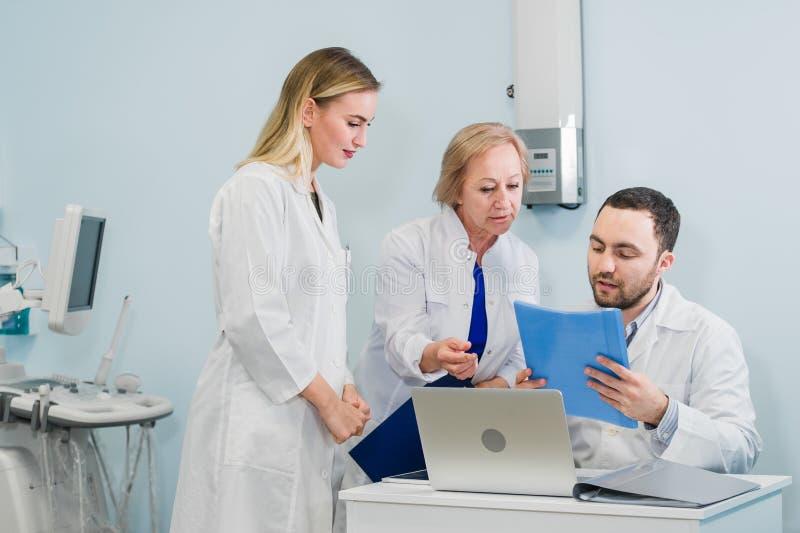 一起谈论三位的医生照片治疗新的方式,当开会议在办公室时 使用膝上型计算机的医生 免版税图库摄影