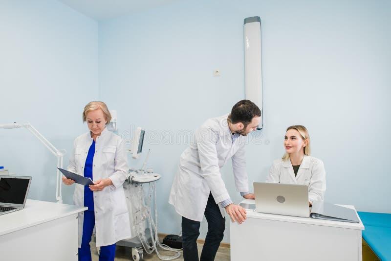 一起谈论三位的医生照片治疗新的方式,当开会议在办公室时 使用膝上型计算机的医生 库存图片