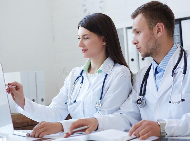 一起谈论两位的医生治疗新的方式,当开会议在办公室时 使用台式计算机的医生 库存图片