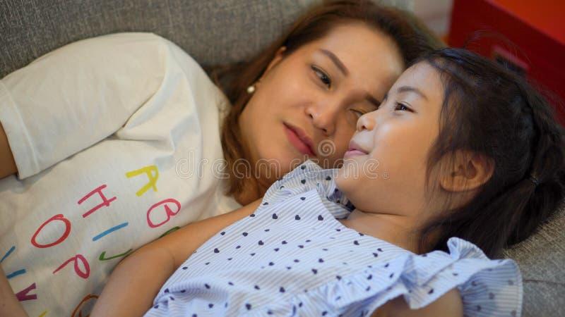 一起谈话的母亲和的女儿放置在沙发和 E 演奏和拥抱在床上的儿童女孩妈妈  免版税库存图片