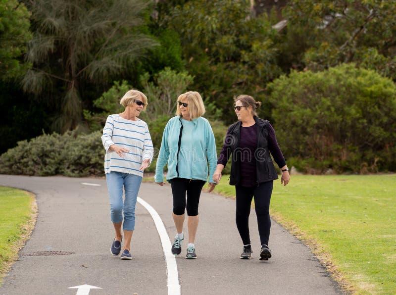 一起走和训练在健康退休生活方式的愉快的活跃老年人妇女 免版税库存照片
