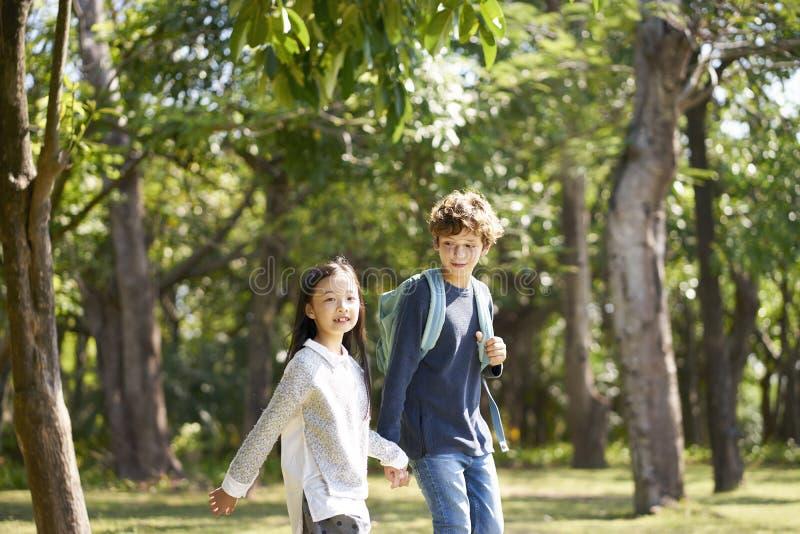 一起走在公园的亚裔和白种人孩子 免版税图库摄影