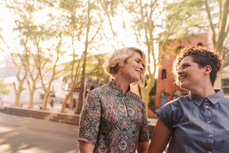 一起走在城市街道上的微笑的年轻女同性恋的夫妇 免版税图库摄影