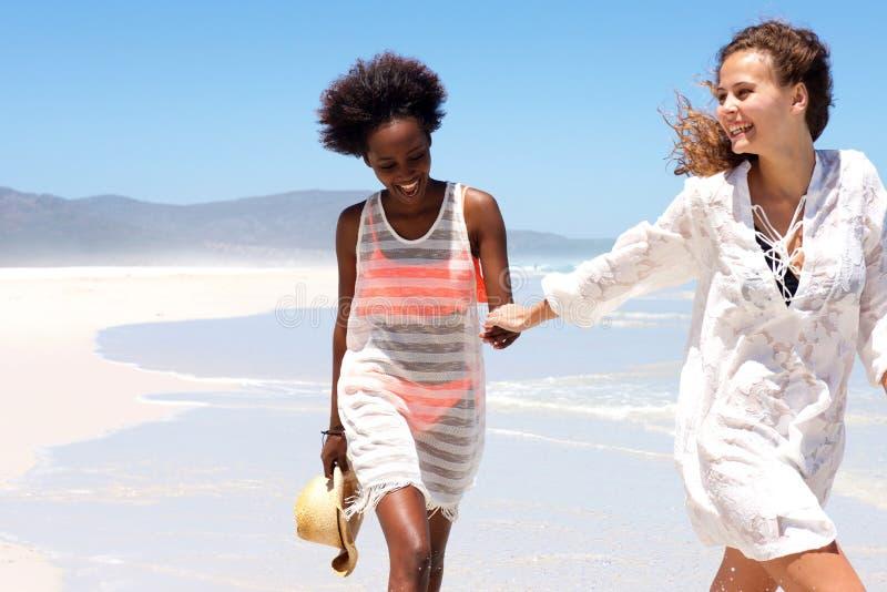 一起走在海滨的微笑的少妇 免版税库存图片