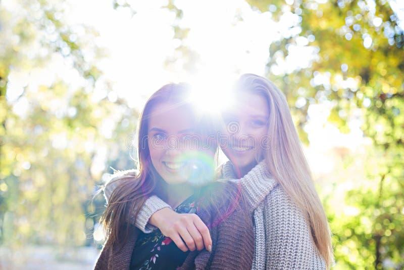 一起走在秋天公园背景中的时兴的美丽的年轻女朋友 获得乐趣和摆在 免版税库存图片