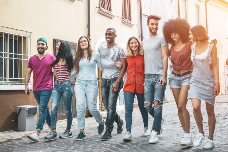 一起走在街道上的小组年轻人 停留在镇的愉快的朋友 免版税库存照片