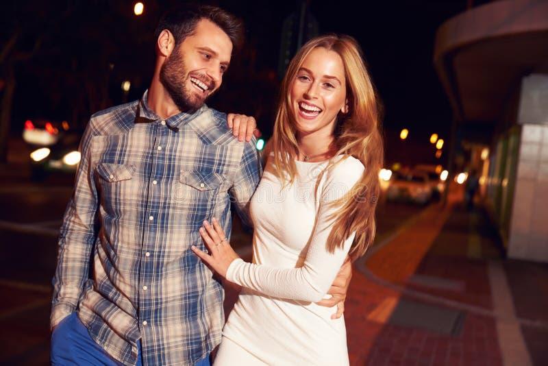 一起走通过镇的夫妇在晚上 免版税库存照片