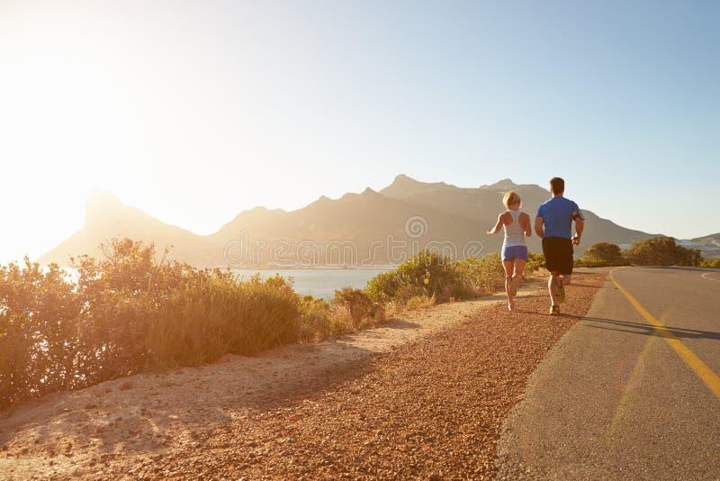 一起跑在一条空的路的男人和妇女 库存照片