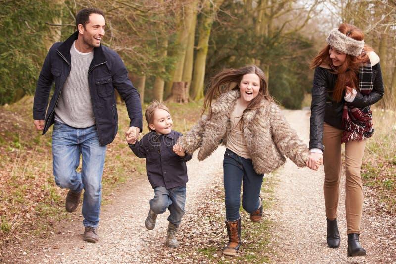 一起跑在冬天乡下步行的家庭 库存图片
