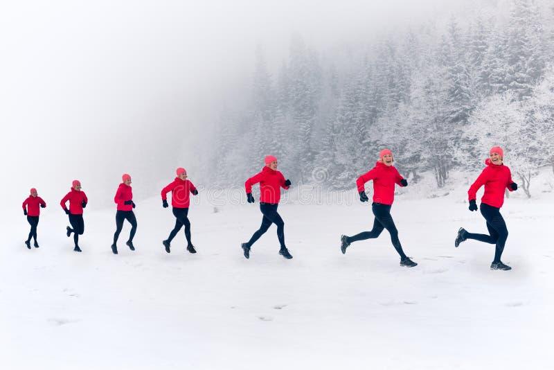 一起跑在冬天山的雪的女孩 体育、健身启发和刺激  库存图片
