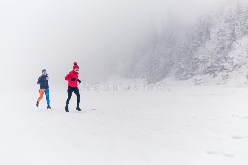 一起跑在冬天山的雪的女孩 体育、健身启发和刺激  图库摄影