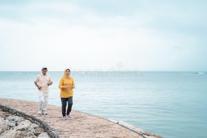 一起跑在海滩的老人和妇女 免版税库存照片