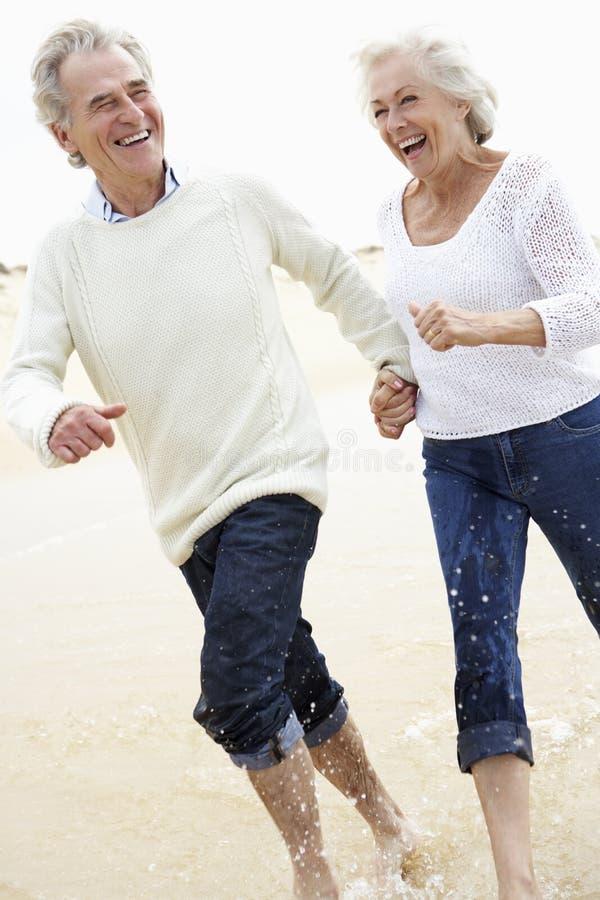 一起跑沿海滩的资深夫妇 免版税图库摄影