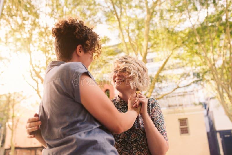 一起跳舞在城市街道上的微笑的年轻女同性恋的夫妇 免版税库存照片