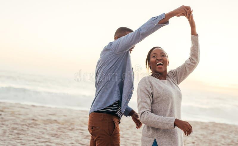 一起跳舞在海滩的笑的非洲夫妇在日落 免版税库存照片