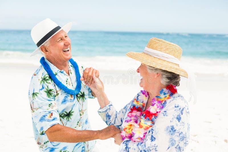 一起跳舞在海滩的资深夫妇 库存图片