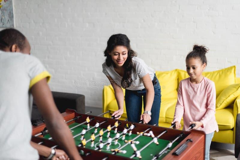 一起踢桌橄榄球的愉快的家庭 库存图片