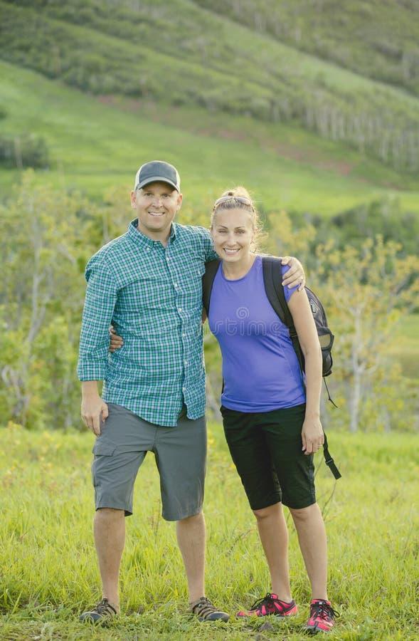 一起远足在一个美丽的山山坡的逗人喜爱的年轻夫妇 库存照片