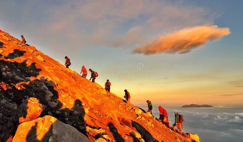 一起远足山攀登人峰顶 免版税库存照片