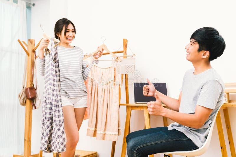 一起选择布料的年轻亚洲恋人夫妇在家 拿着2件礼服,男朋友赞许的女朋友 免版税库存照片