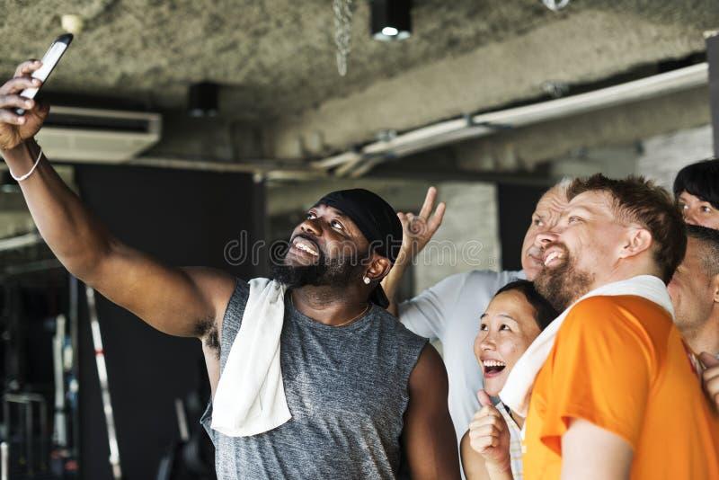 一起采取selfie的小组不同的朋友在健身房 图库摄影