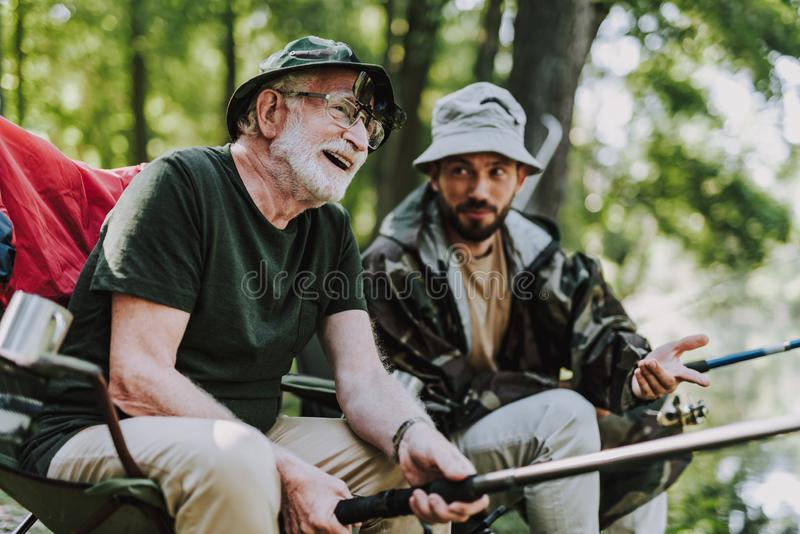 一起钓鱼与他的儿子的快乐的年迈的人 免版税图库摄影