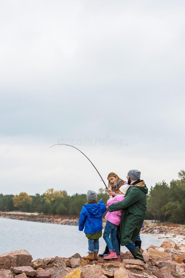 一起钓鱼激动的年轻的家庭 免版税库存照片