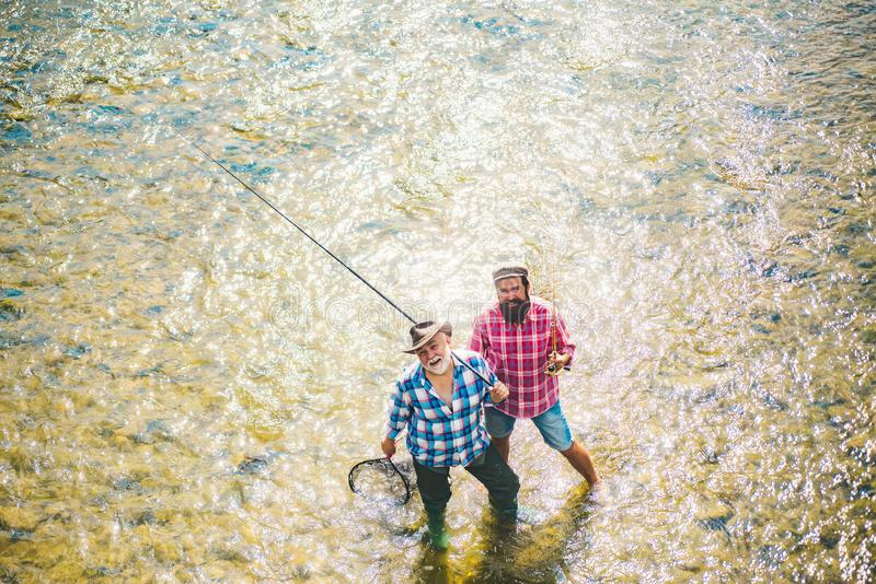 一起钓鱼的父亲和的男孩 斑鳟鱼 河的飞行钓鱼者 一起放松的父亲和的儿子 免版税库存照片