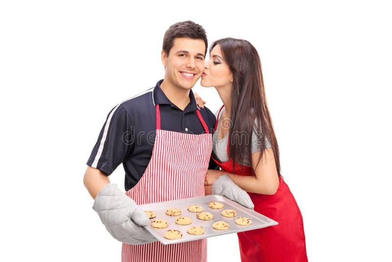 一起年轻夫妇烘烤曲奇饼 免版税库存照片