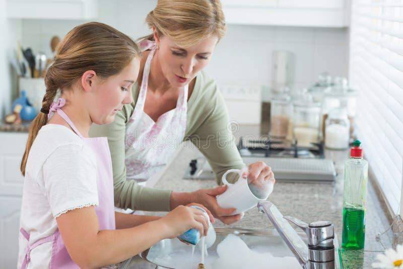 一起洗涤的母亲和的女儿  免版税库存图片