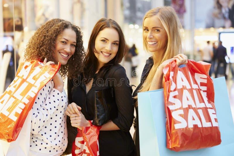 一起购物在购物中心的三个女性朋友 免版税库存照片