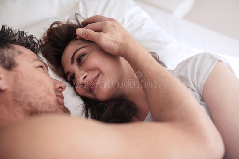 一起说谎在床上的浪漫夫妇 库存照片