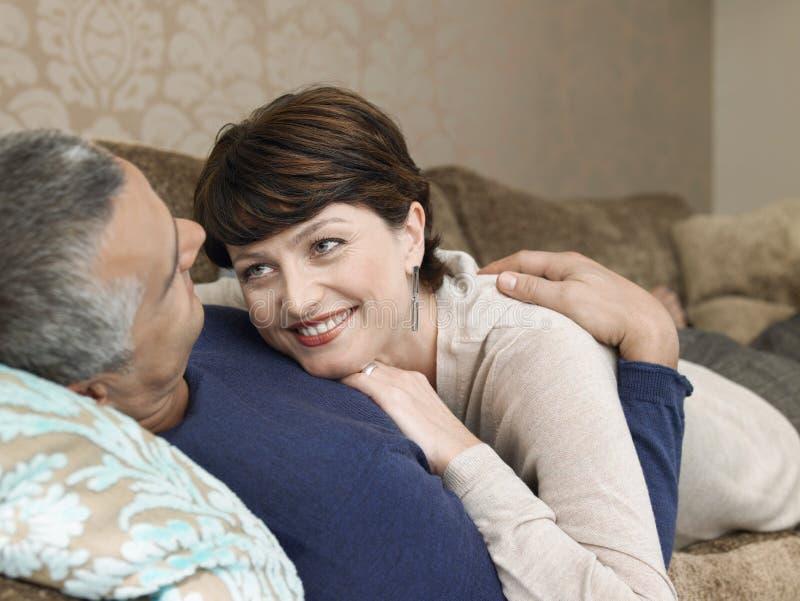 一起说谎在沙发的爱恋的夫妇 库存照片