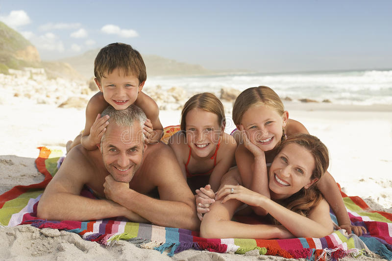 一起说谎在海滩的愉快的家庭 库存图片