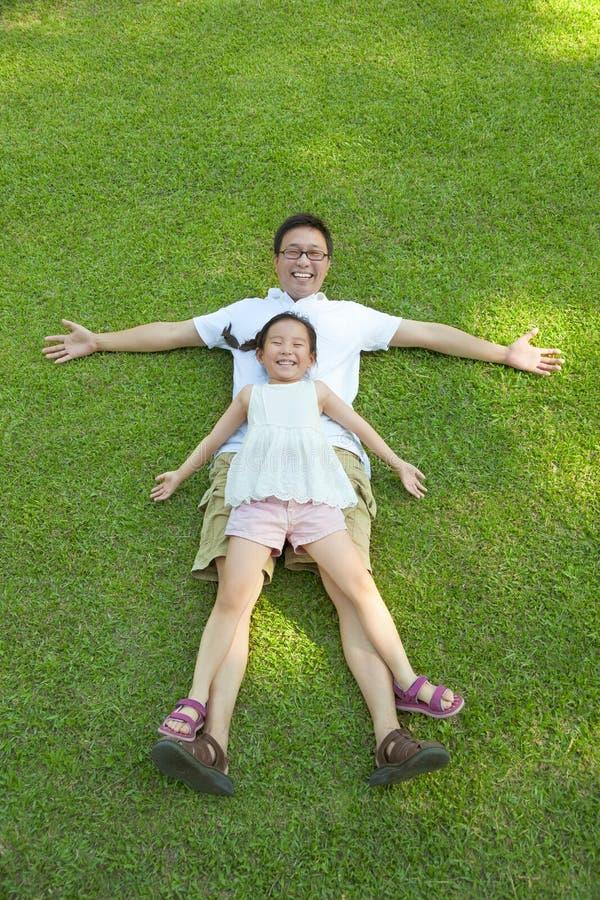 一起说谎在草甸的父亲和女儿 免版税库存图片